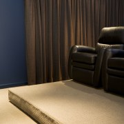 View of a home theatre with screen, projector, floor, flooring, furniture, interior design, light, lighting, room, table, textile, wall, wood, black, orange
