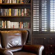 Image of dark stained library shelving and cabinetry bookcase, chair, furniture, home, interior design, library, living room, shelf, shelving, window, wood, black