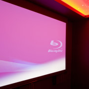 View of projector screen in home theatre. - display device, light, magenta, pink, projection screen, projector accessory, sky, red, pink
