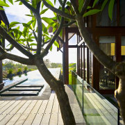View of outdoor area and pool with landscaping, arecales, house, leisure, outdoor structure, plant, tree, wood, black