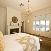 View of bedroom with chandelier, wooden flooring, rug, bed frame, bedroom, ceiling, estate, floor, home, interior design, property, real estate, room, suite, wall, window, orange