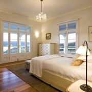 View of bedroom with chandelier, wooden flooring, rug, bed frame, bedroom, ceiling, estate, floor, home, interior design, property, real estate, room, wall, window, wood, orange, brown