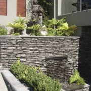 View of garden which includes a stone wall courtyard, garden, landscape, landscaping, plant, stone wall, walkway, wall, yard, black, white