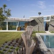 Exterior view of the outdoor area with pool, architecture, estate, home, house, landscape, plant, real estate, sky, water, teal