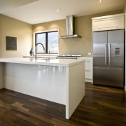 view of a show home kitchen where the cabinetry, countertop, floor, flooring, hardwood, home, interior design, kitchen, laminate flooring, real estate, room, wood, wood flooring, gray, brown