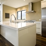view of a show home kitchen where the cabinetry, countertop, floor, home, interior design, kitchen, property, real estate, room, sink, white, brown