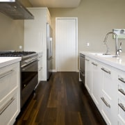 view of a show home kitchen where the bathroom, cabinetry, countertop, floor, flooring, hardwood, home, interior design, kitchen, property, real estate, room, sink, wood, gray, brown