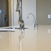 view of a show home kitchen where the floor, flooring, glass, product design, tap, gray