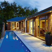 View of the swimming pool and outdoor entertainment backyard, cottage, estate, facade, home, house, lighting, property, real estate, siding, swimming pool, villa, window, brown