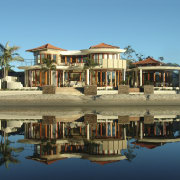 Exterior view of tropical resort-style house which was cottage, estate, home, house, mansion, palm tree, property, real estate, reflection, residential area, resort, sky, villa, teal, brown