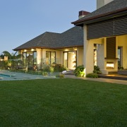 View of contemporary home with light-toned and beige backyard, estate, facade, hacienda, home, house, landscaping, lawn, leisure, mansion, property, real estate, residential area, resort, swimming pool, villa, window, green