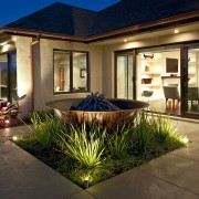 View of contemporary home with light-toned and beige backyard, courtyard, estate, facade, home, house, interior design, lighting, property, real estate, villa, window, brown