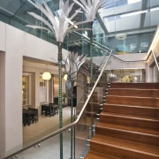 View of stairwell with glass balustrade, steel handrails, architecture, building, condominium, daylighting, glass, handrail, interior design, lobby, mixed use, real estate, stairs, structure, brown, gray