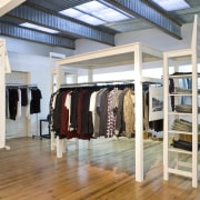nterior view of the clothing displays at the boutique, floor, flooring, wood, gray, white