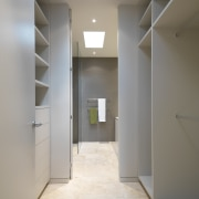 View of a walk-in closet which leads to apartment, architecture, ceiling, daylighting, floor, flooring, hall, home, house, interior design, lighting, property, real estate, room, wall, gray