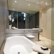 View of bathroom featuring bathtub in a tiled bathroom, interior design, plumbing fixture, product design, room, sink, tap, toilet seat, white, gray