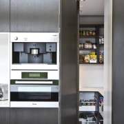 View of kitchen featuring dark-stained oak cabinetry, appliances, home appliance, kitchen, refrigerator, shelf, shelving, white, black