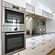 View of kitchen which features white cabinetry with cabinetry, countertop, cuisine classique, home appliance, interior design, kitchen, kitchen appliance, gray, white