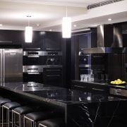 View of an apartment kitchen which features solid cabinetry, countertop, home appliance, interior design, kitchen, room, black