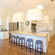 View of a kitchen featuring long island with ceiling, chair, countertop, dining room, floor, flooring, furniture, hardwood, home, interior design, kitchen, laminate flooring, light fixture, product design, room, table, wood flooring, orange