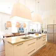 View of a kitchen island with composite stone cabinetry, countertop, cuisine classique, floor, interior design, kitchen, room, white, orange