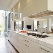 View of large marble island with cooktop, sinks cabinetry, countertop, cuisine classique, interior design, kitchen, real estate, gray