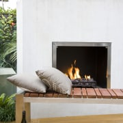 View of outdoor entertaining area which features a fireplace, furniture, hearth, heat, table, wood burning stove, white