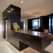 View of the kitchen where the island extends furniture, interior design, living room, table, brown, black