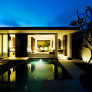 This Balinese villa is clad in limestone, sandstone architecture, estate, evening, home, house, landscape lighting, lighting, property, real estate, reflection, sky, villa, window, black