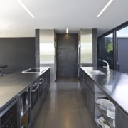 View of open-plan kitchen featuring polished concrete flooring, countertop, house, interior design, kitchen, property, real estate, white