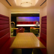 View of the social hub which features red architecture, ceiling, interior design, light, lighting, room, suite, wall, orange, red