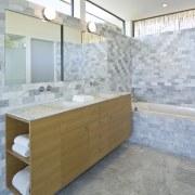 View of a bathroom which features a marble bathroom, bathroom cabinet, countertop, floor, flooring, home, interior design, room, sink, tile, gray