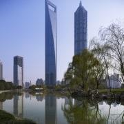 View of the Shanghai World Financial Centre in building, city, cityscape, condominium, corporate headquarters, daytime, landmark, metropolis, metropolitan area, reflection, sky, skyline, skyscraper, tower, tower block, tree, water, teal