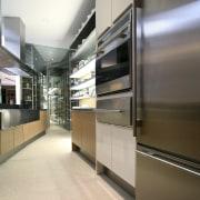 View of wet kitchen featuring large rangehood and architecture, floor, interior design, kitchen, gray