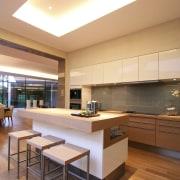 View of open-plan kitchen area featuring island woodgrain architecture, ceiling, countertop, daylighting, floor, hardwood, interior design, kitchen, real estate, wood flooring, orange, brown