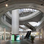 Interior view of the large public concourse between architecture, building, ceiling, convention center, daylighting, interior design, lobby, shopping mall, structure, gray, black