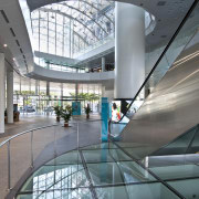 Interior view of the large public concourse between architecture, building, daylighting, glass, headquarters, interior design, leisure centre, metropolitan area, mixed use, shopping mall, tourist attraction, gray