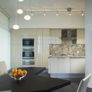 View of the kitchen featuring Pashmina Heartland granite cabinetry, ceiling, countertop, interior design, kitchen, light fixture, lighting, room, table, under cabinet lighting, gray
