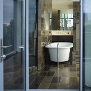 View of the master bath featuring a Per architecture, bathroom, door, floor, glass, home, interior design, real estate, window, black