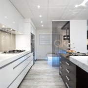 This kitchen by Yellowfox features an island with countertop, interior design, kitchen, white