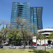 Exterior view of One East Melbourne developed by architecture, arecales, building, city, commercial building, condominium, corporate headquarters, daytime, downtown, headquarters, landmark, metropolis, metropolitan area, mixed use, neighbourhood, palm tree, plant, real estate, residential area, sky, skyscraper, tower, tower block, tree, urban area, teal