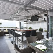 The commercial look of the kitchen is reinforced interior design, outdoor structure, patio, real estate, roof, gray