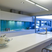 This sleek kitchen in a beach house features architecture, countertop, glass, interior design, kitchen, gray