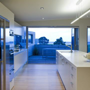 This sleek kitchen in a beach house features interior design, gray