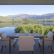 View of kitchen and living area featuring light estate, home, house, lake, landscape, mountain, property, real estate, roof, sky, table, water, gray