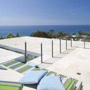 View of rooftop terrace which features paving, outdoor beach, condominium, estate, ocean, outdoor furniture, property, real estate, resort, sea, sky, sunlounger, vacation, teal, white