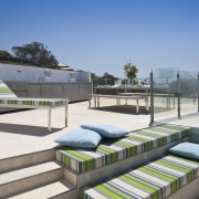 View of rooftop terrace which features paving, outdoor architecture, furniture, outdoor furniture, sunlounger