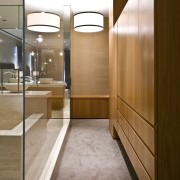 View of contemporary bathroom with mirror wall, white architecture, cabinetry, floor, flooring, furniture, interior design, lobby, room, wood, brown, white