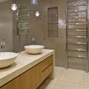View of contemporary bathroom with mirror wall, white bathroom, cabinetry, countertop, floor, flooring, interior design, room, sink, tile, brown