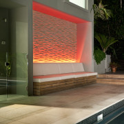 View of sleek poolscape with textured stone wall, architecture, daylighting, glass, hearth, house, interior design, brown